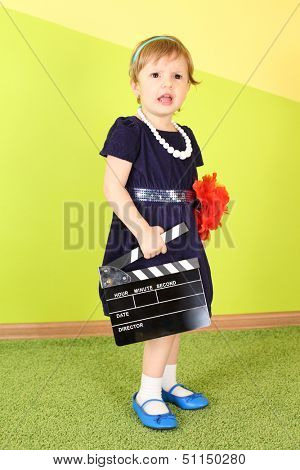 Little girl in a dark blue dress holds a clapstick in her hand