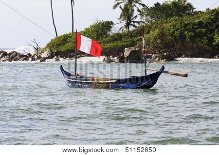 Typical African Fishing Boat With Red And White Flag In The Water With An Island Backdrop