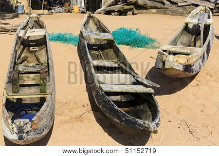 Three Old Dugout Canoes On The Beach With Nets