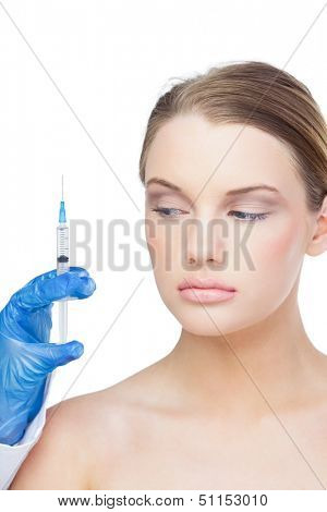Calm beautiful blonde on white background holding surgical needle