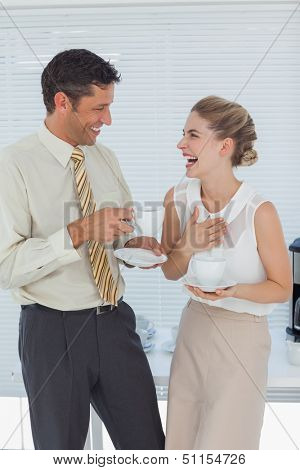 Stylish workmates laughing while having coffee together in break room