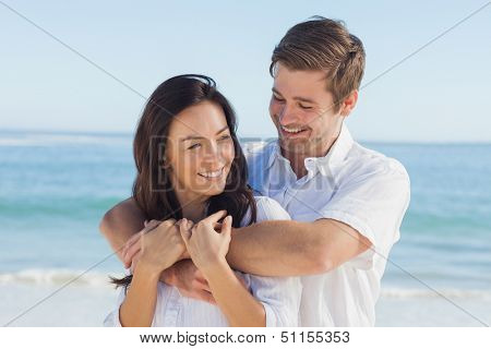 Cheerful couple relaxing and embracing on the beach during summer