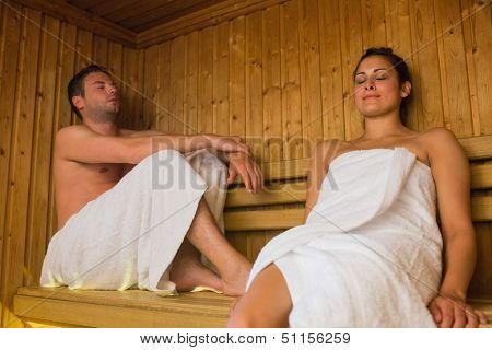 Happy couple relaxing in a sauna wearing towels and smiling