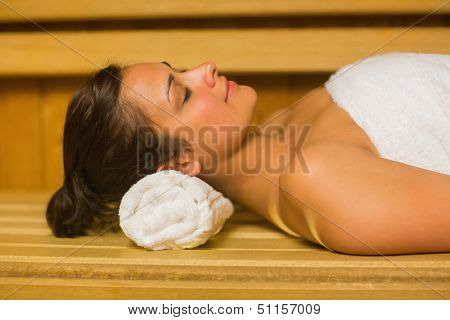 Peaceful brunette relaxing in a sauna lying down wearing white towel