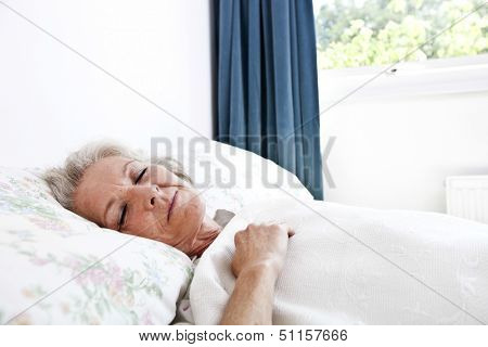 Senior woman sleeping in bedroom at home