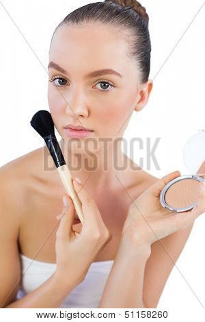 Sensual model with powder compact and powder brush looking at camera