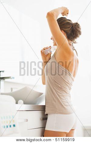 Woman Applying Roller Deodorant On Underarm In Bathroom