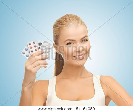health, medicine, beauty concept - young woman with variety of pills