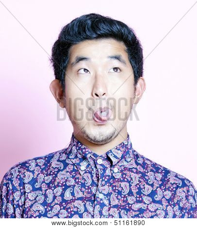 Young Geeky Asian Man in colorful shirt pulling funny face