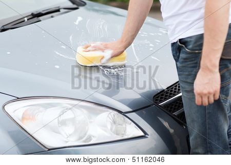 transportation and ownership concept - man washing a car