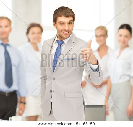 office, buisness, teamwork concept - friendly young smiling businessman with thumbs up