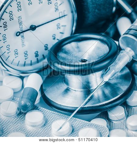Syringe, different pills, stethoscope and sphygmomanometer toned in blue shades