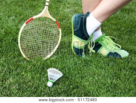 foot of badminton player who stays on grass