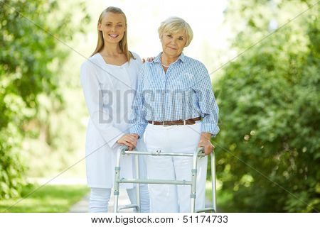 Pretty nurse and senior patient with walking frame looking at camera outside