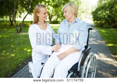Pretty nurse talking to senior patient in a wheelchair in park
