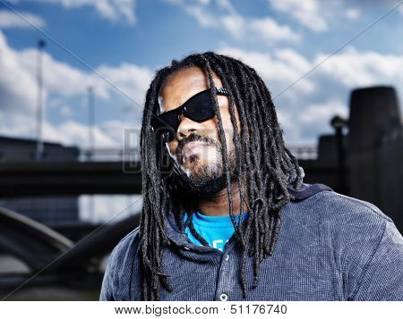 cool african man showing dreads with lens flare