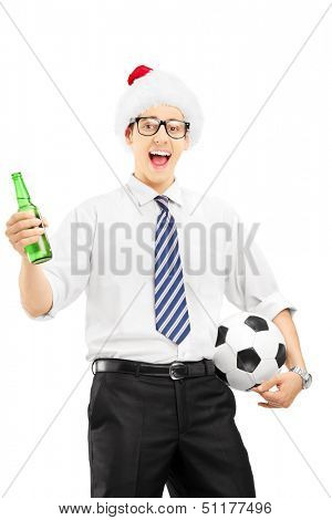 Smiling male with santa hat holding a beer bottle and soccer ball isolated on white background