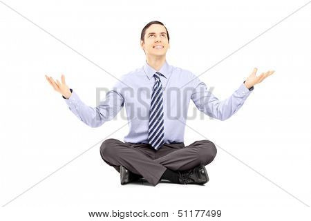 Young businessman sitting on a floor and gesturing with his hands isolated on white background