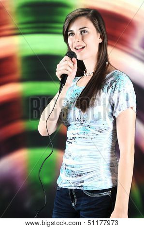 A vertical image of a beautiful teen soloist happily singing into a microphone.