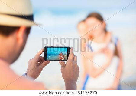 Young man making photo of his wife and daughter at tropical beach. Focus on camera