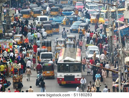 HYDERABAD, ANDHRA PRADESH, INDIA - AUGUST 29: Shoppers and traffic weave about the busy bazaar at the Charminar on August 29 2012. The area is one of the most densely populated in the city.