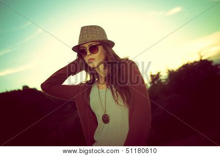 young hipster woman with hat and sunglasses outdoor shot at sunset retro colors