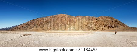 A solitary person walks out on the salt pans of Badwater Basin in Death Valley, California USA.