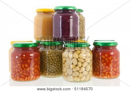 Row glass pots with canned vegetables isolated over white background