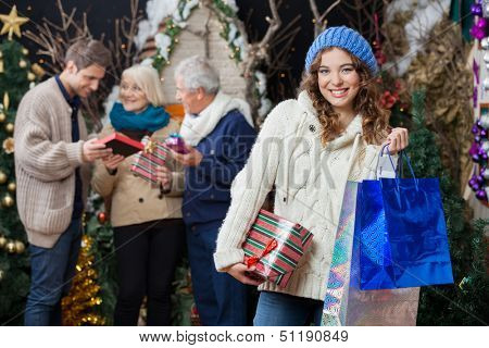 Portrait of beautiful young woman holding Christmas presents and shopping bags with family standing in background at store