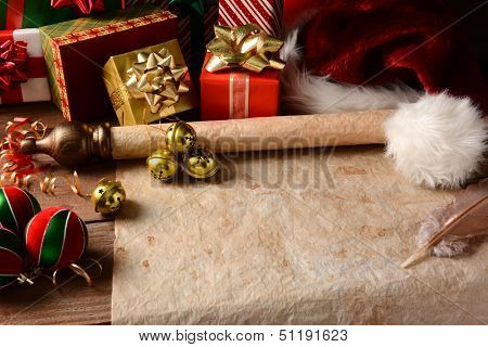 A Christmas Still Life with an old parchment scroll, presents, ornaments and a Santa Hat. Closeup in horizontal format with strong side light.