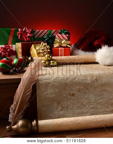 A Christmas Still Life with an old parchment scroll, presents, ornaments and a Santa Hat. Closeup in vertical format with a light to dark red background.