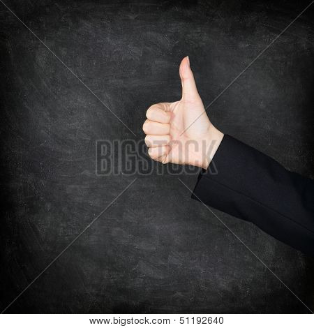 Thumbs up hand on blackboard / chalkboard background. Woman hand sign of approval and succes. Teacher or female student concept image. Black blackboard texture background icon.