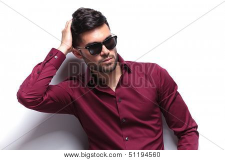 young casual man passing his hand through his hair while looking away from the camera. on white background