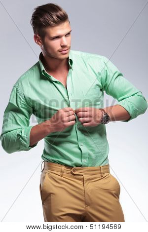 young casual man unbuttoning his shirt while looking away from the camera. on light gray background