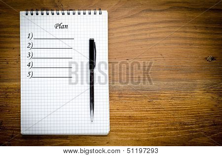 Black notebook with pen on a wood background