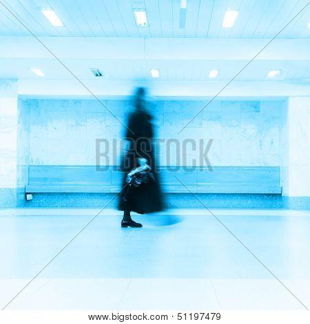Blurred passenger walking at subway station.