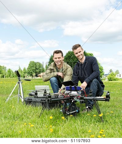 Portrait of happy male engineers with laptop and digital tablet by UAV at park