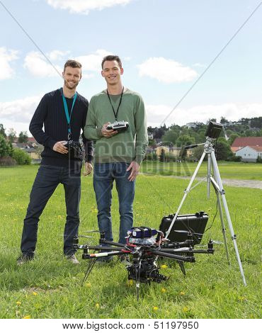 Happy young engineers standing by UAV helicopter and tripod in park