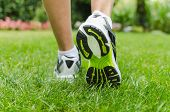 foto of sprinter  - Woman running on green grass in summer - JPG