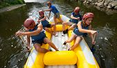 stock photo of down jacket  - A group of friends in an inflatable raft moving down a river - JPG