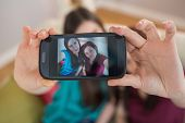 pic of selfie  - Two happy friends on the couch taking a selfie with smartphone at home in the living room - JPG