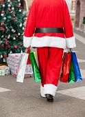 Rear view of Santa Claus with shopping bags walking in courtyard
