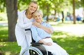stock photo of wheelchair  - Pretty nurse and senior patient in a wheelchair looking at camera outside - JPG