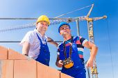 stock photo of bricklayer  - Two proud construction site workers or bricklayers standing on house project directing the crane with a remote control - JPG