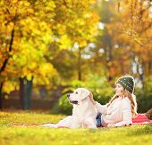 foto of tilt  - Female lying on a green grass with her labrador retriever dog in a park - JPG