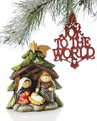 A small nativity scene under the branches of a Christmas tree with an ornament saying,