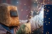 pic of protective eyewear  - Heavy industry welder worker in protective mask hand holding arc welding torch working on metal construction - JPG
