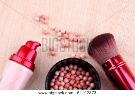 Composition with concealer, powder balls and brush on wooden background