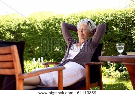 Elder Woman Resting In Backyard Garden