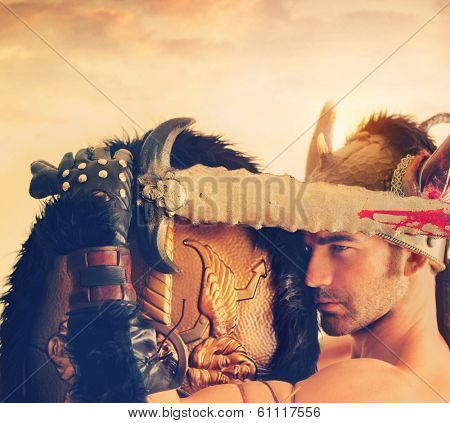 Powerful ancient warrior with bloody sword and helmet beneath a dramatic sky and overall vintage toning for antique effect